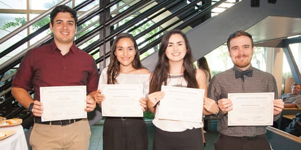 Four students holding their awards