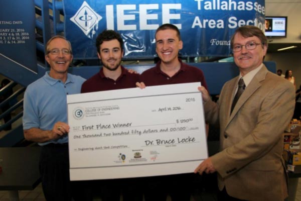 Engineering Interim Dean Bruce Locke (far right) and Entrepreneur in Residence Mike Devine present the winners, Anthony Giordan and Thor Cutler, their 1st Place Prize.