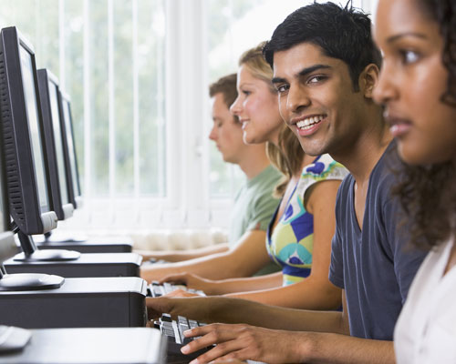 Student smiles at a computer