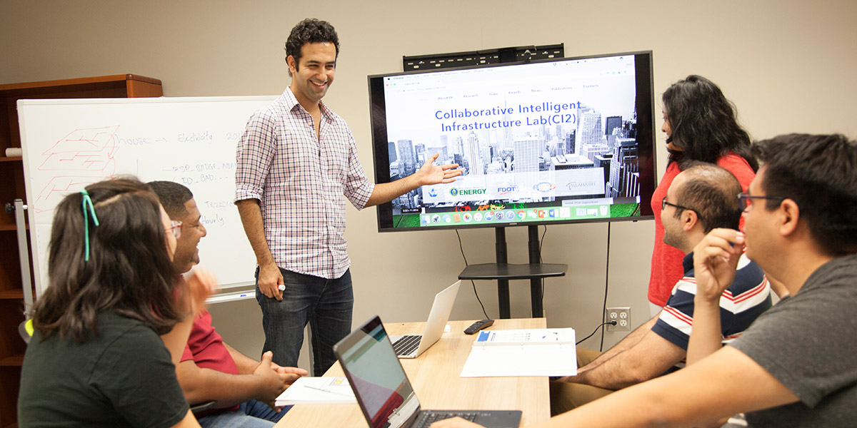 Research professor with graduate students discussing collaborative intelligence