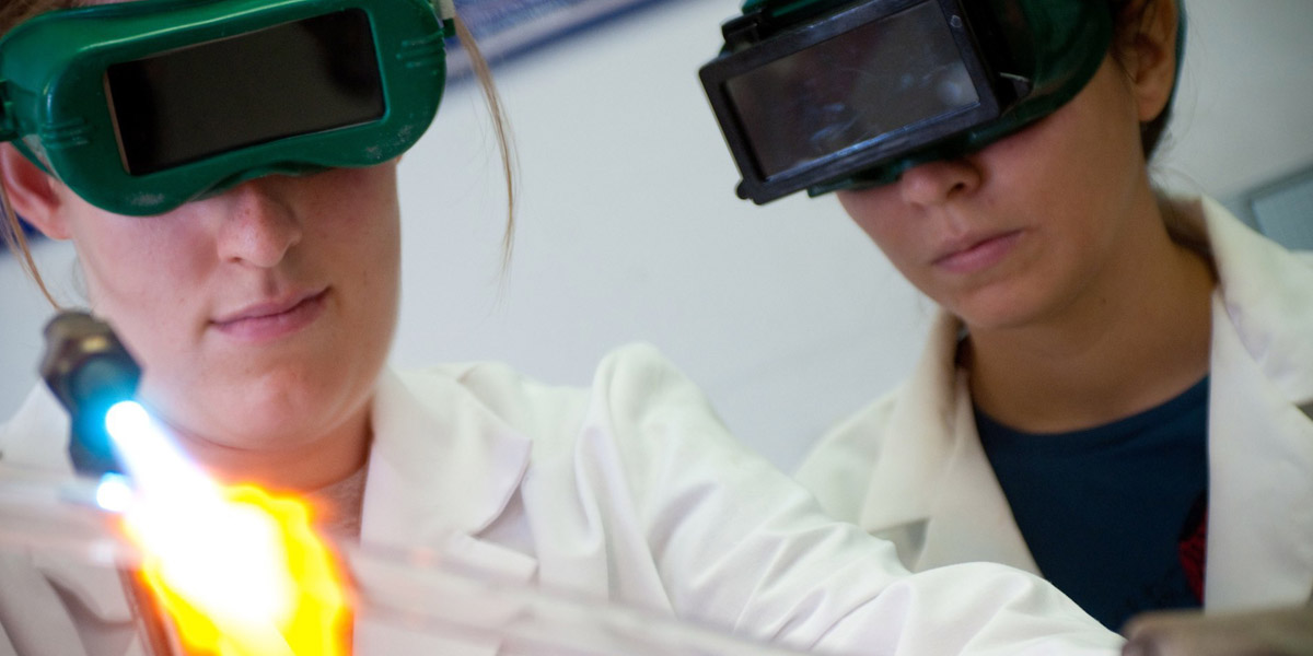 Two female students working in a lab facility with a blowtorch